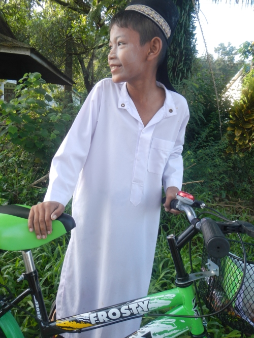Muslim boy on a green FROSTY bike